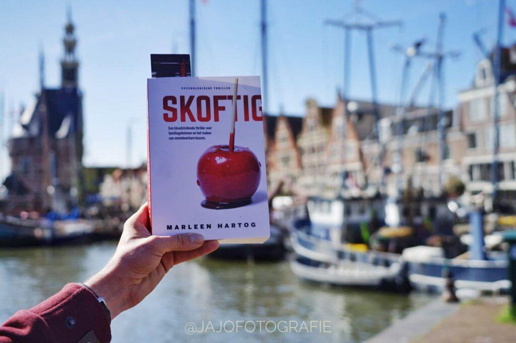 Het boek Skoftig scherp in beeld, op de achtergrond de mooie oude haven van Hoorn.